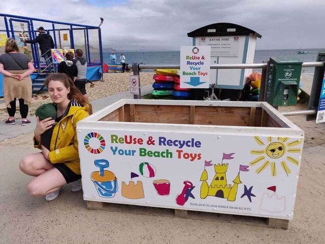 Pallet-sized toy box at lyme with kneeling young woman carrying baby next to it