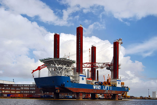 This is the Wind Lift 1 jack-up vessel in Germany. Jack-up vessels are typically used to assemble offshore wind turbines. Great pillars are dropped down from the ship to the sea bed and the vessel is raised up out of the water to provide a stable platform. Cranes are then used to position the giant wind turbine components (blades can be 100 metres long and the nacelle can be 70 tonnes)  Photo by Carschten